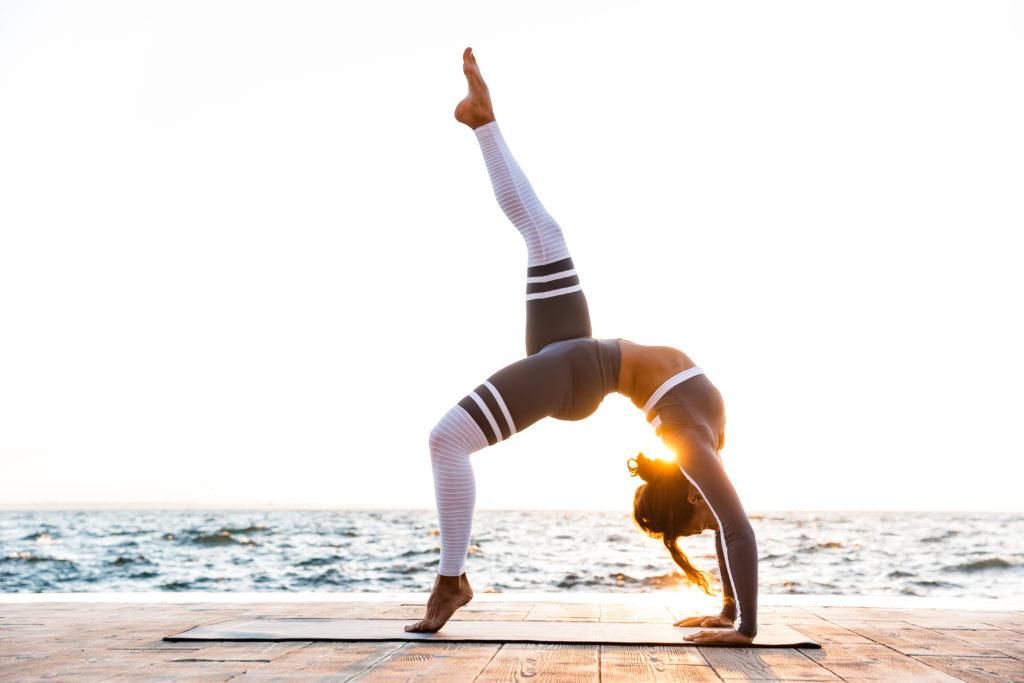 Kobieta ćwicząca jogę na plaży
